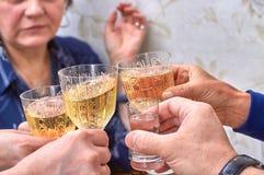 Champagneexponeringsglas och ett skott av vodka i händerna av gästerna som kväv alkohol royaltyfri bild