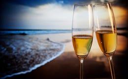 Champagneexponeringsglas på den tropiska stranden - exotiskt nytt år Arkivbild