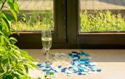 Champagneexponeringsglas på fönsterbrädan i solljus fotografering för bildbyråer