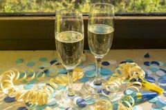 Champagneexponeringsglas på fönsterbrädan med konfettier royaltyfria foton