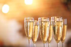 Champagneexponeringsglas på guld- bakgrund Champagne med den isolerade flygballonger och santa hatten Arkivfoton