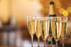 Champagneexponeringsglas på guld- bakgrund Champagne med den isolerade flygballonger och santa hatten Royaltyfri Foto