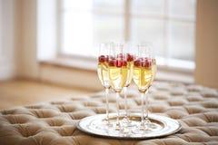 Champagneexponeringsglas på silvermagasinet Champagne med den isolerade flygballonger och santa hatten arkivbild