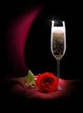 Champagneexponeringsglas på svart och rött silke Arkivfoton