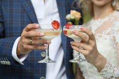 Champagneexponeringsglasen i händerna av nygifta personerna royaltyfri fotografi