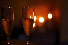 Champagneflöjter framme av stearinljusljus royaltyfri bild