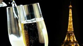Champagneflöjter med guld- bubblor på guld- blänker gnistrandeEiffeltorn på svart nattbakgrund, feriejul
