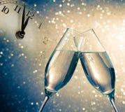 Champagneflöjter med guld- bubblor på blå och guld- ljus bokehbakgrund Royaltyfri Bild