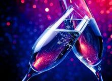 Champagneflöjter med guld- bubblor på blått tonar ljus bokehbakgrund Royaltyfri Bild