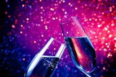 Champagneflöjter med guld- bubblor på blått tonar ljus bokehbakgrund Arkivbilder