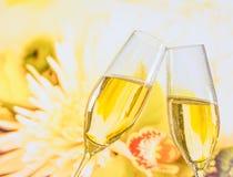 Champagneflöjter med guld- bubblor på bröllop blommar bakgrund Royaltyfri Foto