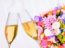 Champagneflöjter med guld- bubblor på bröllop blommar bakgrund Royaltyfri Fotografi