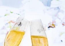 Champagneflöjter med guld- bubblor på bröllop blommar bakgrund Arkivbild