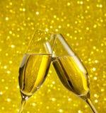 Champagneflöjter med guld- bubblor på guld- ljus bokehbakgrund Royaltyfria Bilder