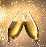 Champagneflöjter med guld- bubblor på ljus bokehbakgrund Royaltyfri Foto