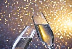 Champagneflöjter med guld- bubblor på ljus bokehbakgrund Arkivfoto