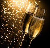 Champagneflöjter med guld- bubblor på mörk guld- ljus bokehbakgrund Royaltyfri Bild