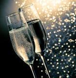 Champagneflöjter med guld- bubblor på mörker - blå ljus bokehbakgrund Arkivbilder