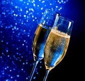 Champagneflöjter med guld- bubblor på mörker - blå ljus bokehbakgrund Fotografering för Bildbyråer
