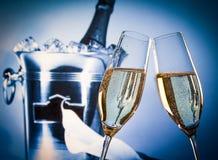 Champagneflöjter med guld- bubblor som är främsta av champagneflaskan i hink Arkivfoton