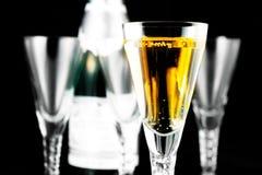 Champagneflöjter och buteljerar på svart royaltyfri fotografi