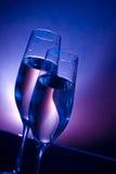 Champagneflöjter på stångtabellen på blå och violett ljus bakgrund för mörker - Arkivbild