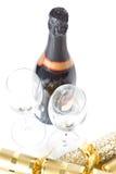 Champagneflaska och exponeringsglas med xmas-smällare Royaltyfria Bilder