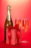 Champagneflaska, två vinexponeringsglas och gåvaask arkivfoto