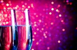 Champagneflöjter med guld bubblar på bakgrund för blått- och violettonljusbokeh Royaltyfria Foton