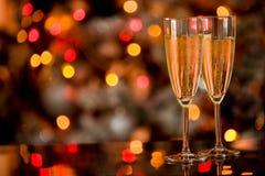 Champagner sulla Tabella di vetro con la priorità bassa di Bokeh Immagine Stock