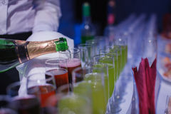 Champaign. being pored into glasses. banquet table. Blue light Royalty Free Stock Photos