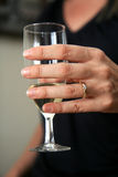 Champaign and Ring. A woman wearing a gold ring holds a glass of champaign royalty free stock photos