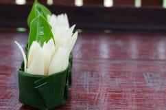 Champaka branco na bacia verde da folha da banana na terra de madeira Foto de Stock