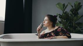 Champanhe bebendo da jovem mulher do encanto, relaxando na banheira após um dia de trabalho duro A mulher atrativa bebe o champan filme