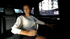 Champanhe bebendo da mulher cansado no assento traseiro do carro, conduzindo em casa com motorista privado imagem de stock royalty free
