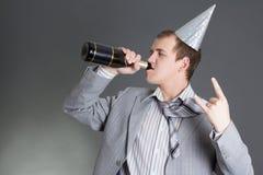 Champanhe bebendo do homem de negócios novo sobre o fundo cinzento Fotografia de Stock