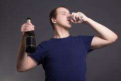 Champanhe bebendo do homem novo sobre o fundo cinzento Fotos de Stock Royalty Free