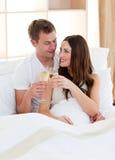 Champanhe bebendo dos pares Intimate que encontra-se na cama Foto de Stock
