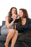Champanhe da bebida de duas mulheres que senta-se em um sofá Imagem de Stock Royalty Free