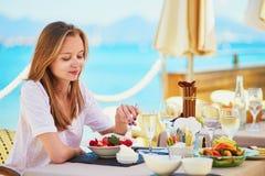 Champanhe da mulher e frutos bebendo comer no restaurante da praia durante seus vagabundos das férias o mar Fotografia de Stock Royalty Free