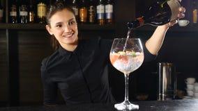 Champanhe de derramamento do barkeeper fêmea em um vidro Barman feliz no uniforme preto 4K vídeos de arquivo