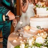 Champanhe de derramamento do noivo nos vidros perto de um bolo de casamento foto de stock royalty free