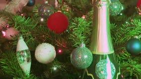 Champanhe do vinho espumante entre o abeto do Natal decorado por bolas do ` s do ano novo vídeos de arquivo