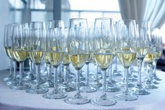Champanhe meio cheio ou vidros borbulhantes indicado em uma tabela coberta no pano de tabela branco Foto de Stock