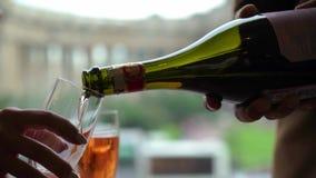 Champanhe ou vinho espumante cor-de-rosa de derramamento ao vidro da garrafa Cidade europeia no fundo filme