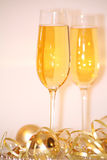 Champers. Two champagne glasses with gold christmas balls and streamers Royalty Free Stock Image