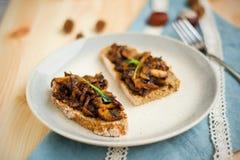 Champiñón frito con ajo en el pan hecho en casa tostado para el desayuno del fin de semana en la placa punteada y con la cinta bl Foto de archivo libre de regalías