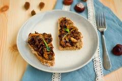 Champiñón frito con ajo en el pan hecho en casa tostado para el desayuno del fin de semana en la placa punteada y con la cinta bl Imagenes de archivo