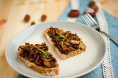 Champiñón frito con ajo en el pan hecho en casa tostado para el desayuno del fin de semana en la placa punteada y con la cinta bl Fotos de archivo