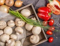 Champiñones en una caja y verduras en una tabla Imágenes de archivo libres de regalías